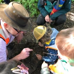 practitioner with earwig on his finger, children looking at bug or searching for more