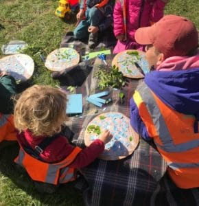 children creating their own earth collages with card and leaves