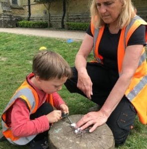 Child tries to create a spark to light a fire under the watchful eye of practitioner