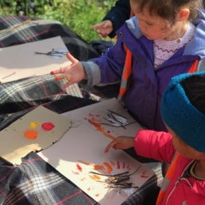 Two children finger paint a fire