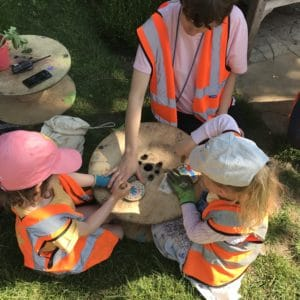 two children with safety gloves using palm drills under supervision